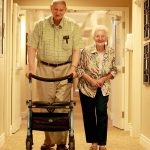 Empire Crossing Retirement Community residents ?John Holmn and his wife Audrey McGilvary walk down the hall for lunch.